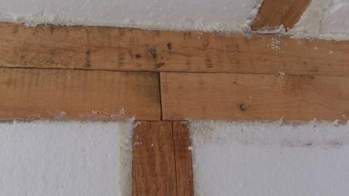 Бруски верхней обвязки стыкуются точно над стойкой стены. На фотографии каркас уже утеплен пенопластом
