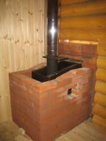 Металлическая печь для бани, обложенная кирпичом
