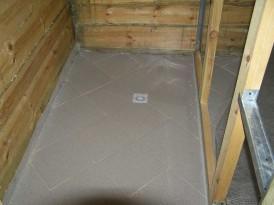 На фото уложенная плитка и смонтированный слив в полу