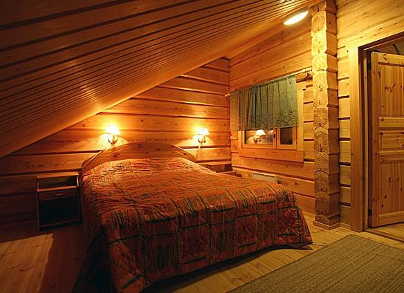 На фото - уютная спальня в мансарде бани