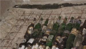 Бутылки закупорены и уложены рядами под сварную сетку