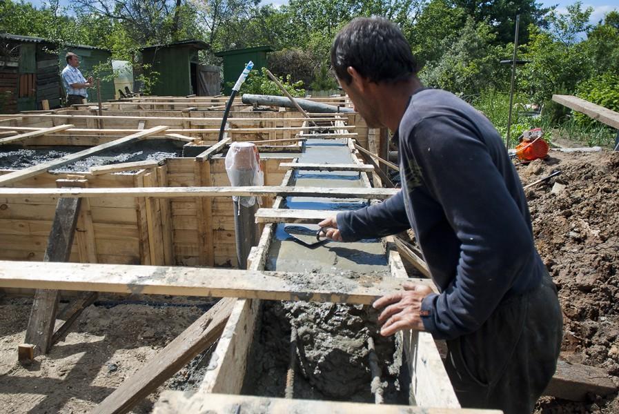 Выравнивание поверхности ленты мастерком в процессе заливки бетона