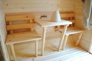 На фото изображен маленький предбанник с решетчатым деревянным полом в бане-бочке