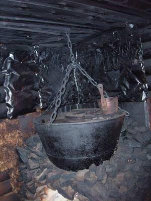 Водяной котел, подвешенный на цепях в бане по-черному