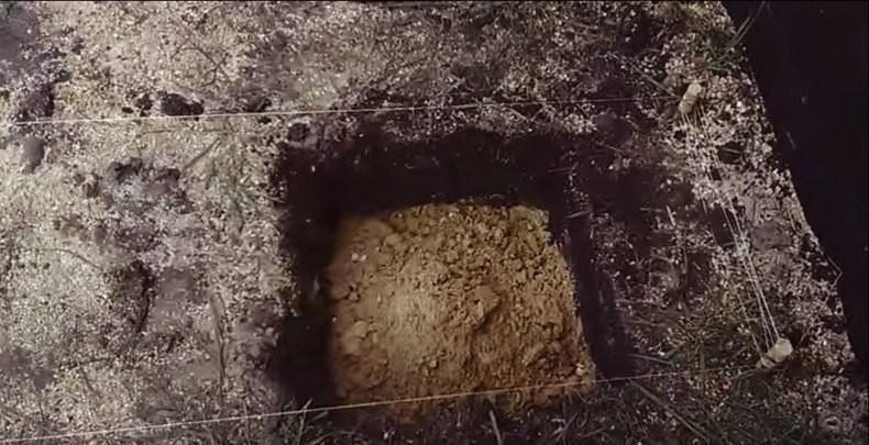 Разметка, вырытая яма для установки опорного столбика и засыпанная песчаная подушка