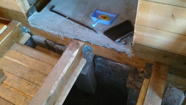 Уложенный лист асбестового картона и заметен монолитный фундамент под ним
