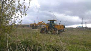 Экскаватор убирает траву и грунт