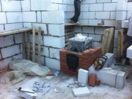 На фото возведение стен бани с одновременной установкой и обкладкой печи