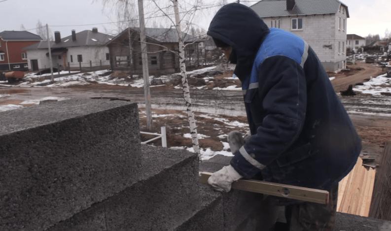 Строитель проверяет положение уложенного блока